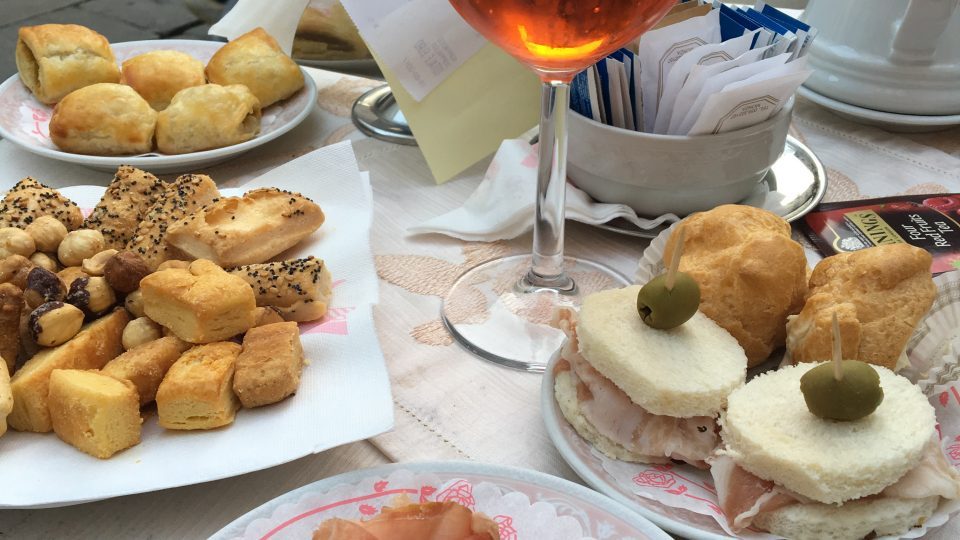 Enjoying aperitivo hour, and every hour in Monza. Image shows an Aperol spritz and a spread of snacks outside a bar in Monza