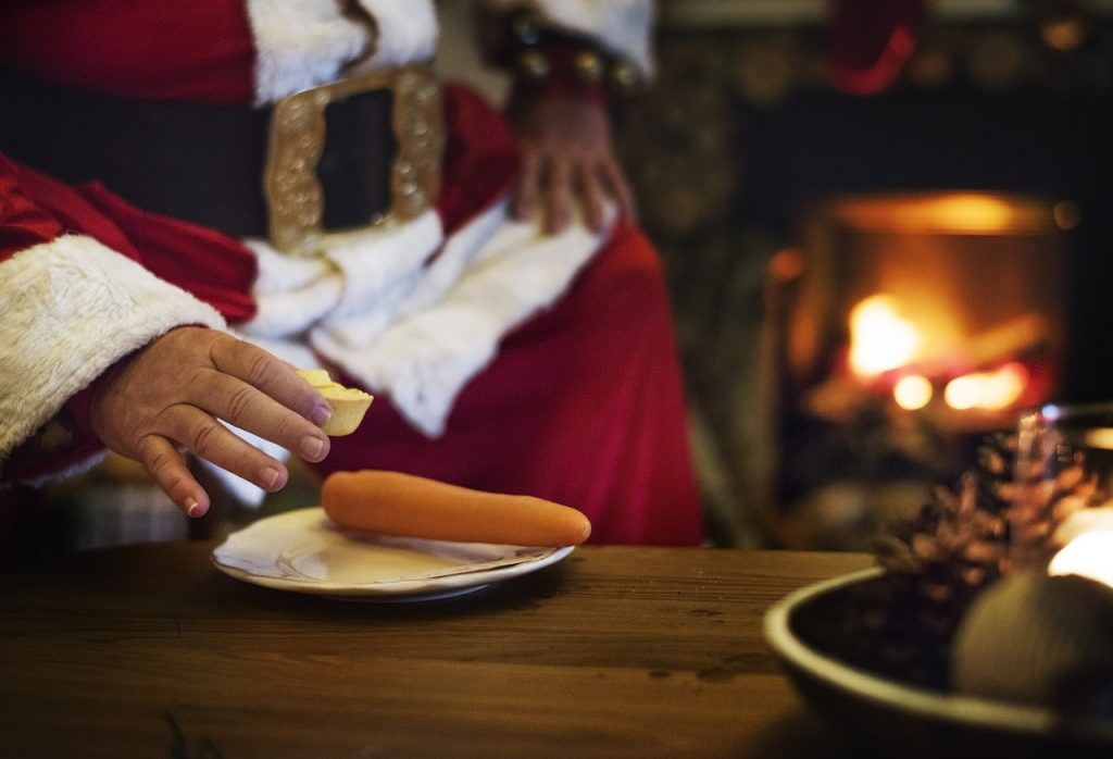 Christmas is coming. Are you ready? Photo shows Santa's hand with a mince pie and a carrot for rudolph, around an open fire