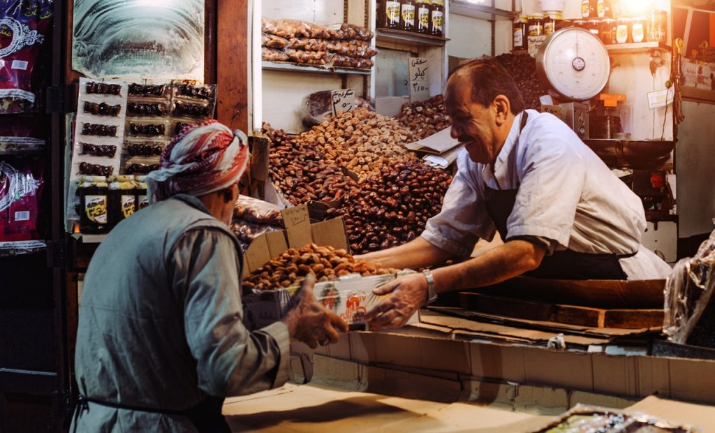 Who is your customer, and why you need to know. Image shows a man selling a woman some dates, surrounded by piles of dates.