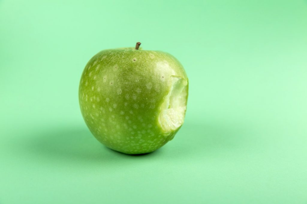 Are you Apple or Microsoft? Image shows a green apple with a bite taken out of it, similar to the Apple logo