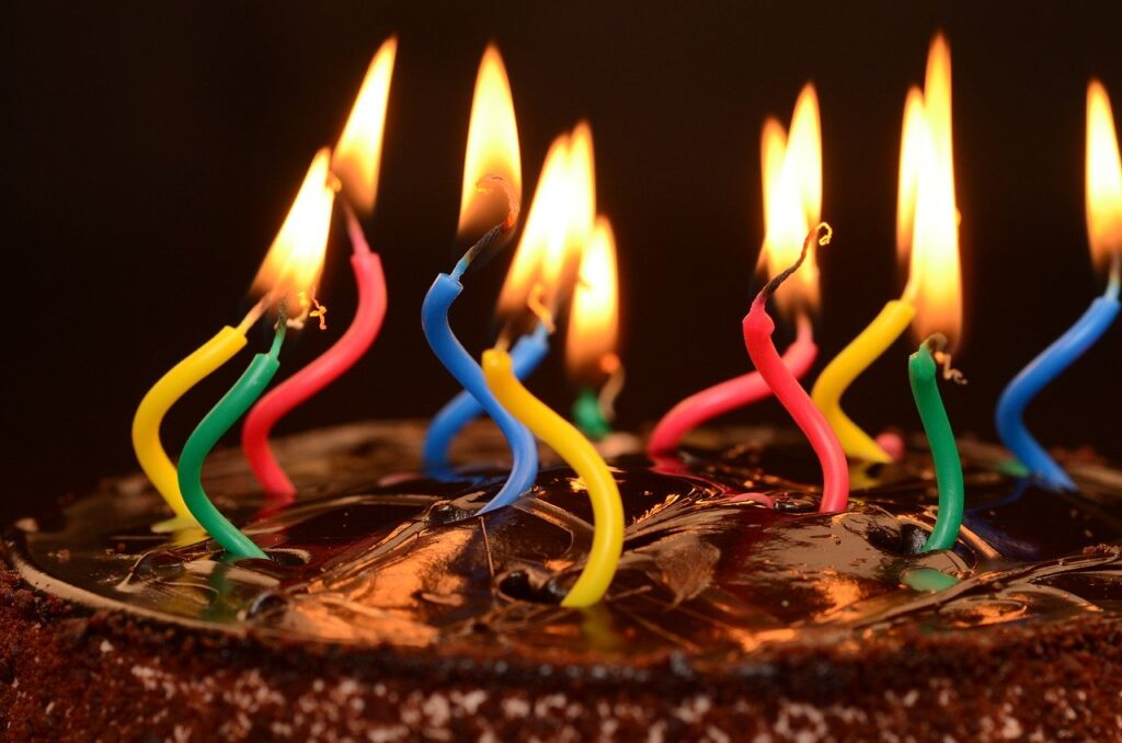 Do you celebrate your business birthday? Image shows a chocolate cake with colourful wiggly candles lit on the top.