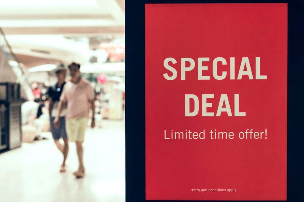 "A red ""special deal, limited time offer"" sign, blurred background of two people in shorts in a typical shopping mall."