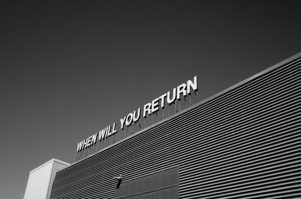 "Black and white image of a building with the phrase ""when will you return"" in large letters across the skyline."