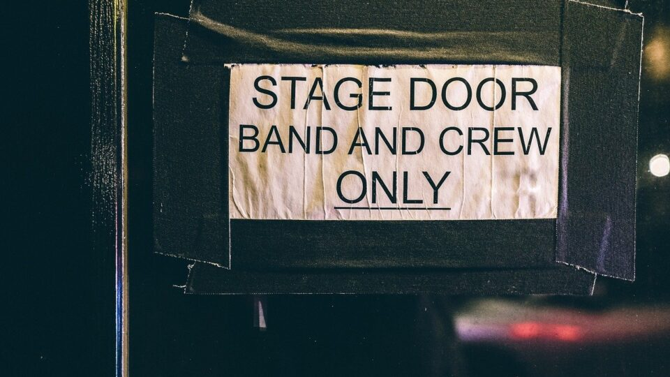 shows sign on a stage door: stage door. band and crew only.