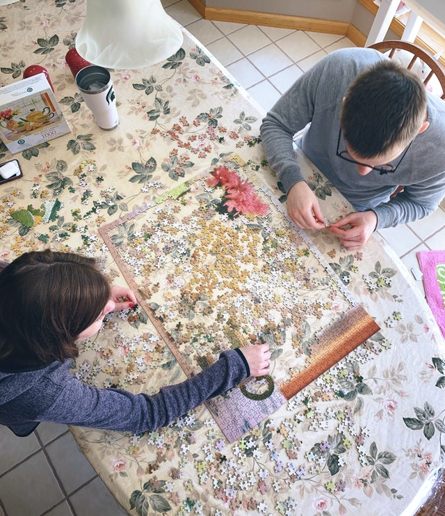 Image shows overhead shot of two people doing a jigsaw together
