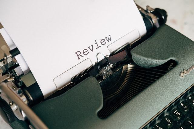 """Shows an old school typewriter with the word """"review"""" typed up on a sheet of paper"""