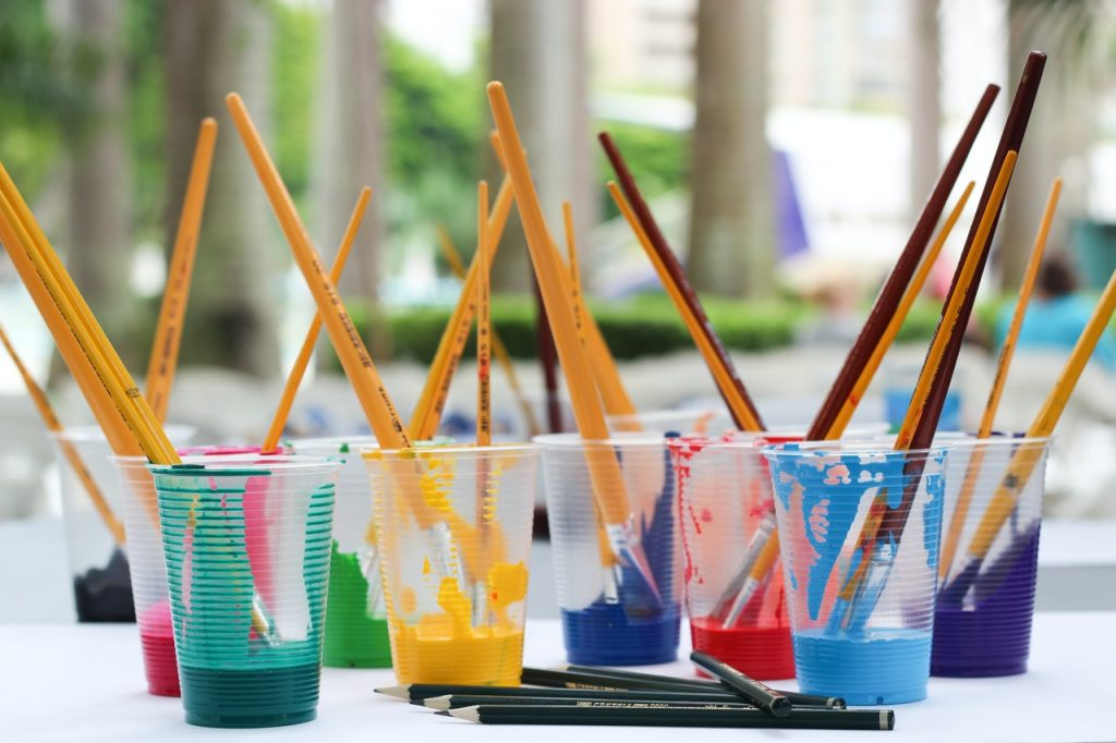 image shows different plastic cups of paint with brushes in them