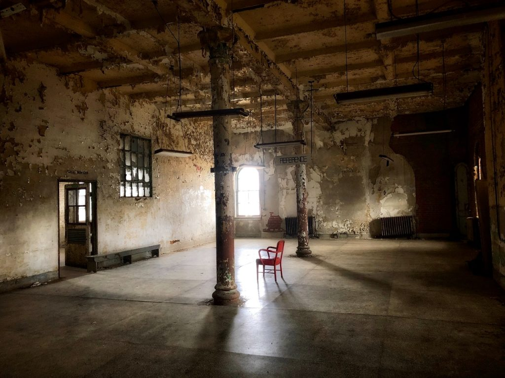 Image shows inside an old empty building with one red chair in the middle