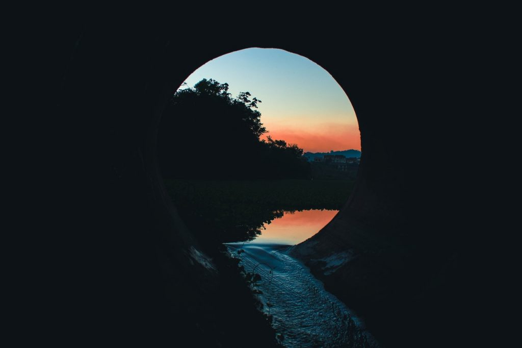 Image shows a sunrise at the end of a tunnel, reflected in water