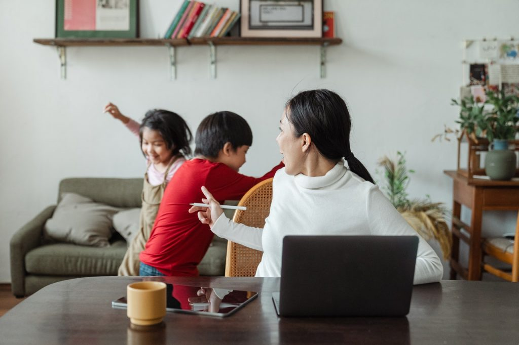 woman trying to work at home with two children playing in the background