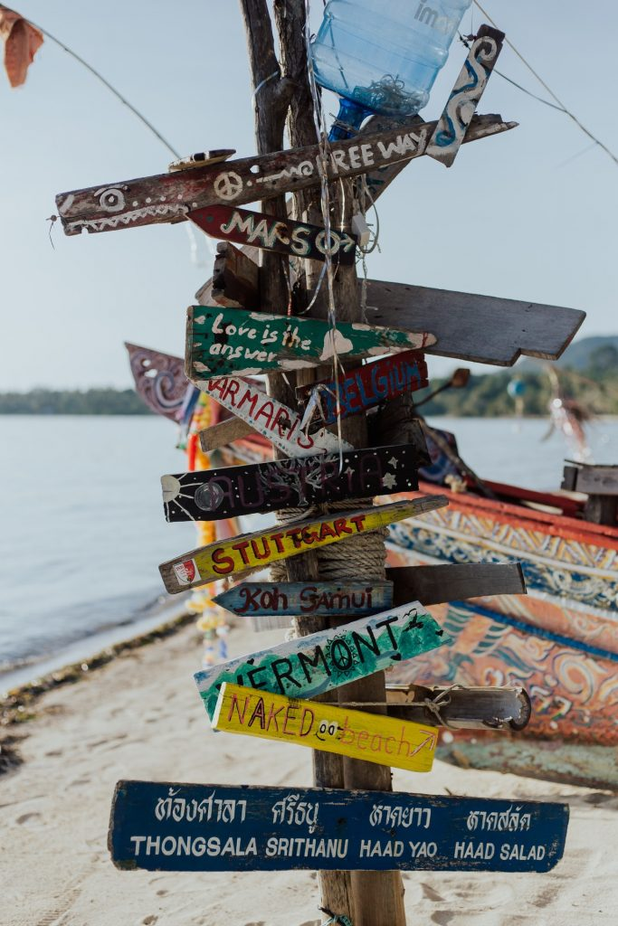a collection of colourful handpainted signposts on a beach with the sea and fishing boats in the background
