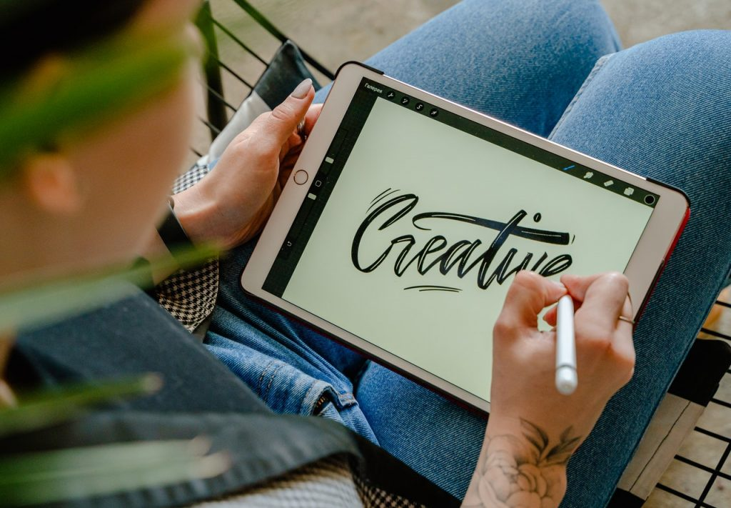 """Image shows person working on a tablet with the word """"creative"""" in a calligrapy type scrip"""