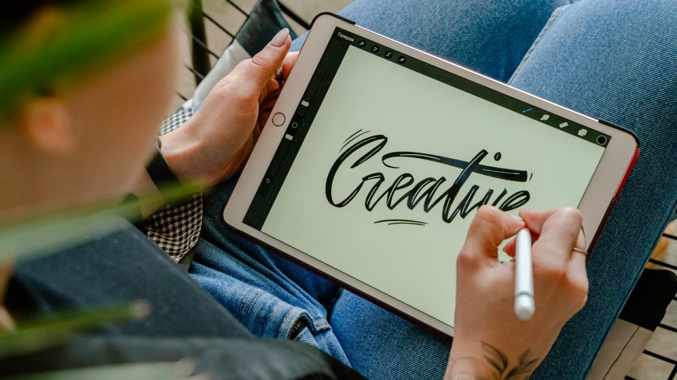 "Image shows person working on a tablet with the word ""creative"" in a calligrapy type scrip"