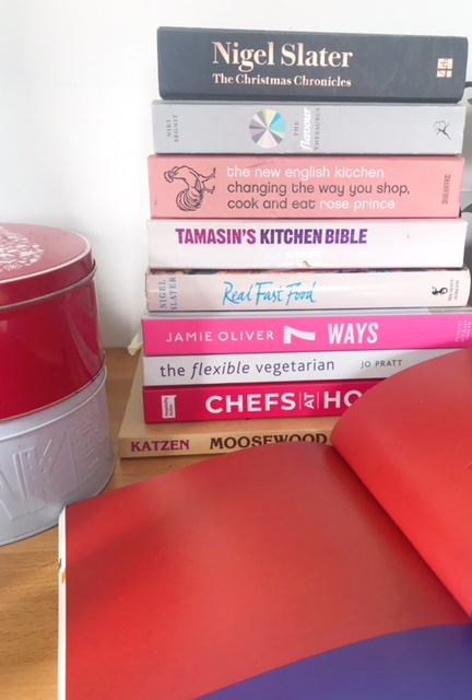 Image shows a pile of cookbooks with one open at the front, Two cake tins, one red, one pale blue, are to the left hand side.