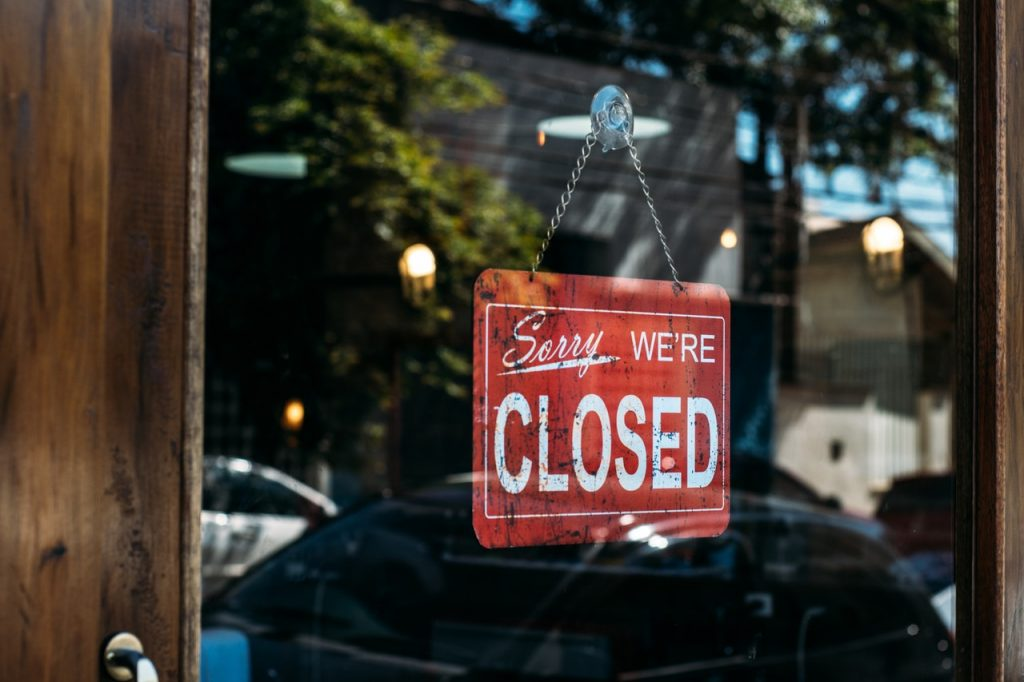 Image shows a sign on a glass door reading Sorry We're Closed