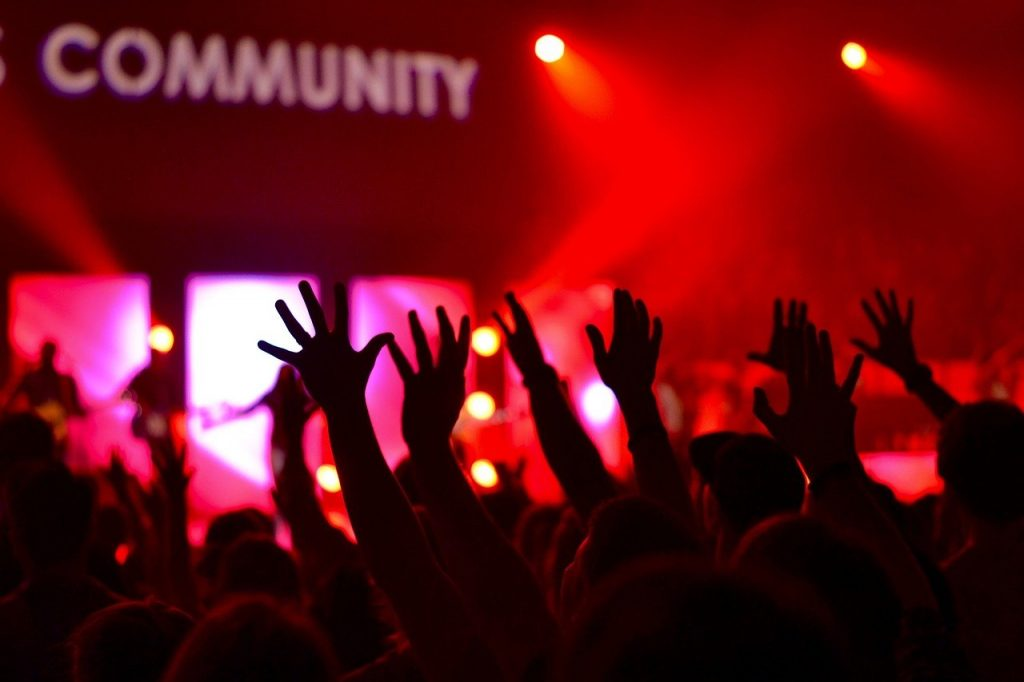 """Image shows people with their hands in the air inside possibly a night club with the word """"community"""" picked out in lights."""