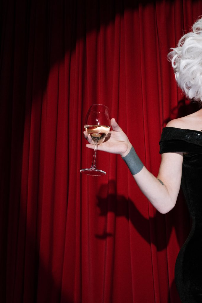 Red velvet curtain with a spotlight falling on a woman's arm holding a glass of wine.