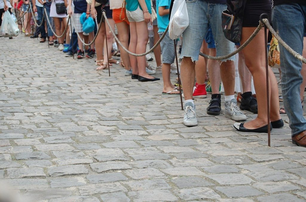 Image shows a long line of people queueing for something with just their legs and feet visible