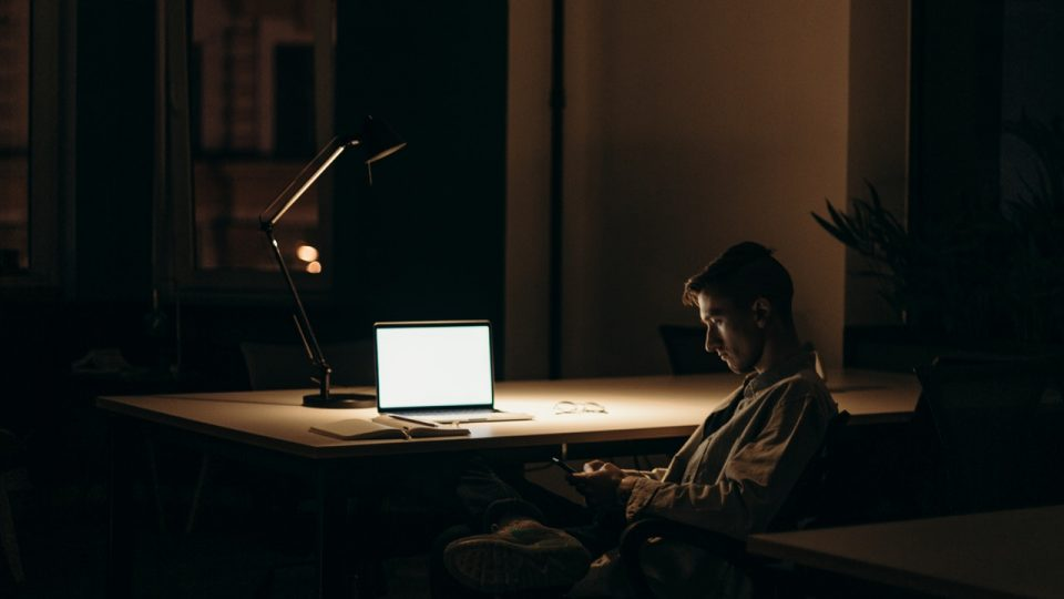Image shows a bright laptop screen in a relatively dark room. We can just make out a man sitting in a chair.