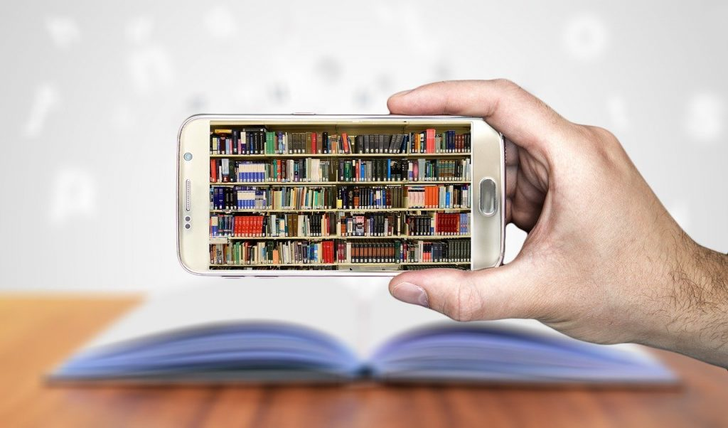 Image shows an image of a library of books on a smartphone screen with a real book on a table in the background How do you collect stories about what you do.
