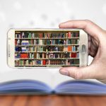 Image shows an image of a library of books on a smartphone screen with a real book on a table in the background
