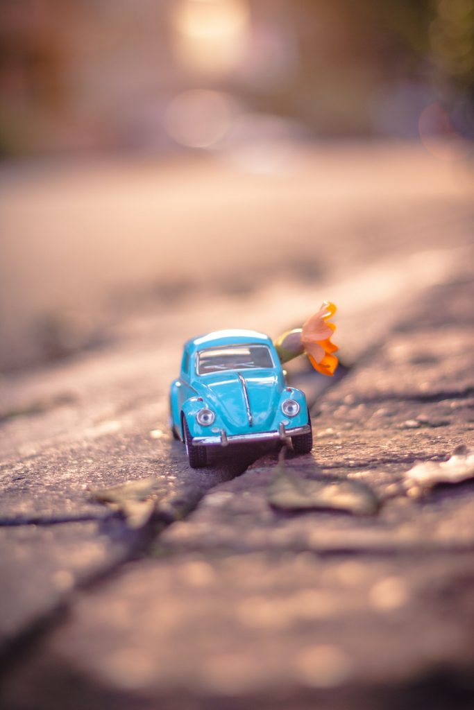 What's your smallest space? Shows a miniature VW Beetle on a pavement with an orange flower.