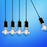 Image shows four lightbulbs in a line with a fifth pulled out to the right to illustrate ideas and momentum