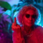 Image shows an older woman with sunglasses on flipping the middle finger