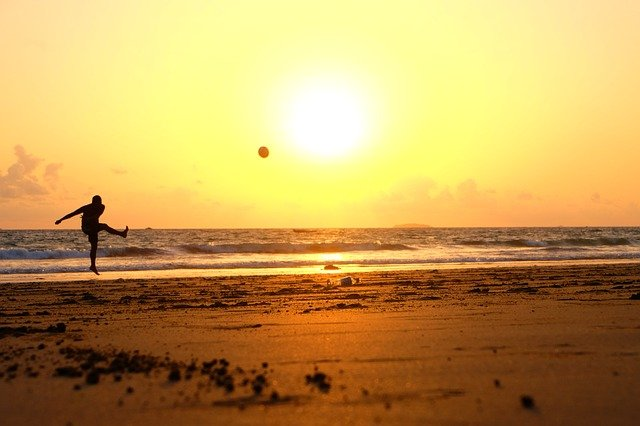 Image shows a person kicking a football on a beach at sunrise or sunset. What to write about when you don't do football.