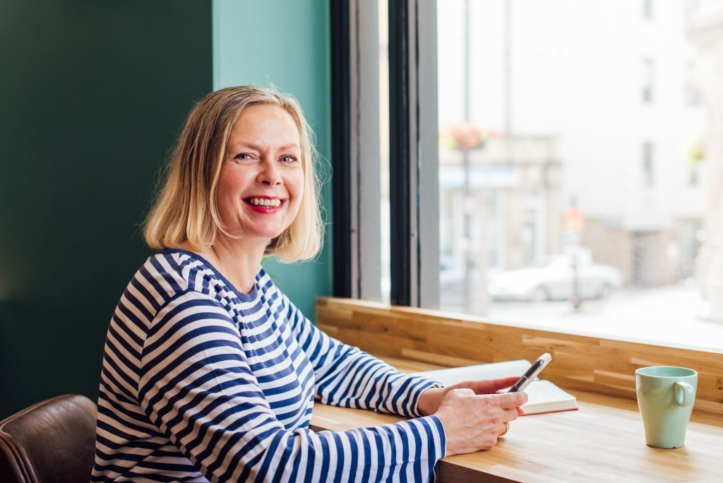 Image shows a woman in a blue and white top holding a mobile phone. The scene outside the window is blurry. | Helen Tarver Freelance Copywriter