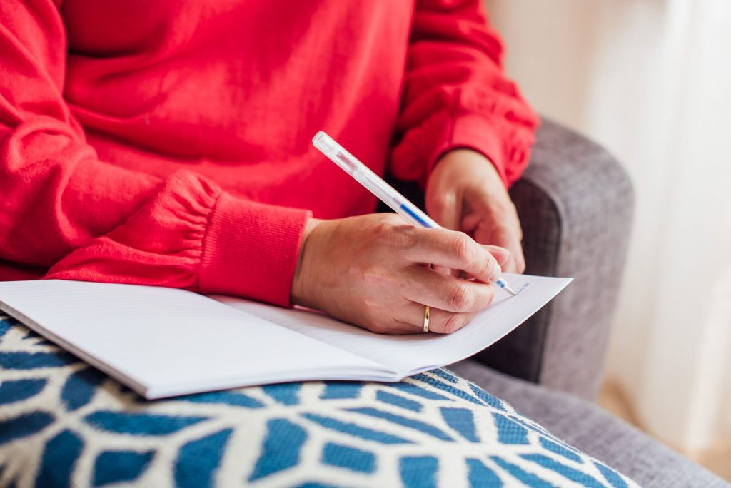 Image shows a woman wearing a red jumper writing in a notebook balanced on a blue and white cushion | Helen Tarver Freelance Copywriter