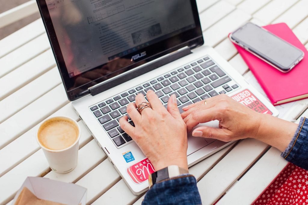 Image shows hands on a laptop keyboard on a white wooden slatted table. There's a cup of coffee to the left, and a mobile phone and pink notebook to the right | Helen Tarver Freelance Copywriter