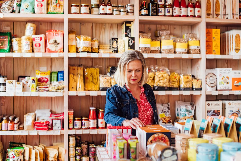 Image shows a woman in a food store looking at something from the display   Helen Tarver Freelance Copywriter