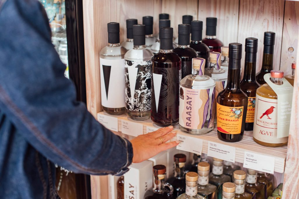 Image shows a shelf of bottles of spirits with a woman's hand reaching towards one of them | Helen Tarver Freelance Copywriter