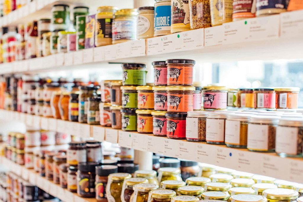 Image shows three shelves of food and drink products, lit from the window behind | Helen Tarver Freelance Copywriter