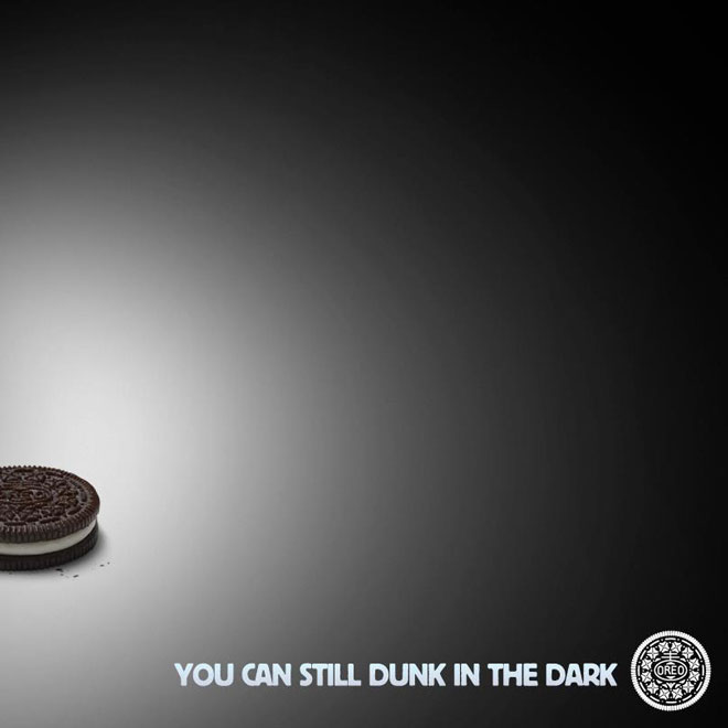 Image is mainly black with a poorly lit Oreo in the bottom left corner. This is the famous Oreo Super Bowl powercut viral content