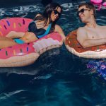 Image shows a man and a woman in a swimming pool in inflatable doughnut rings.