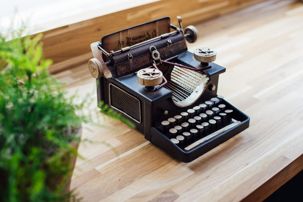 Image shows a vintage looking stenography machine or small typewriter on a wooden background with a green plant to the left side. A technology that is dated and in need of a refresh.