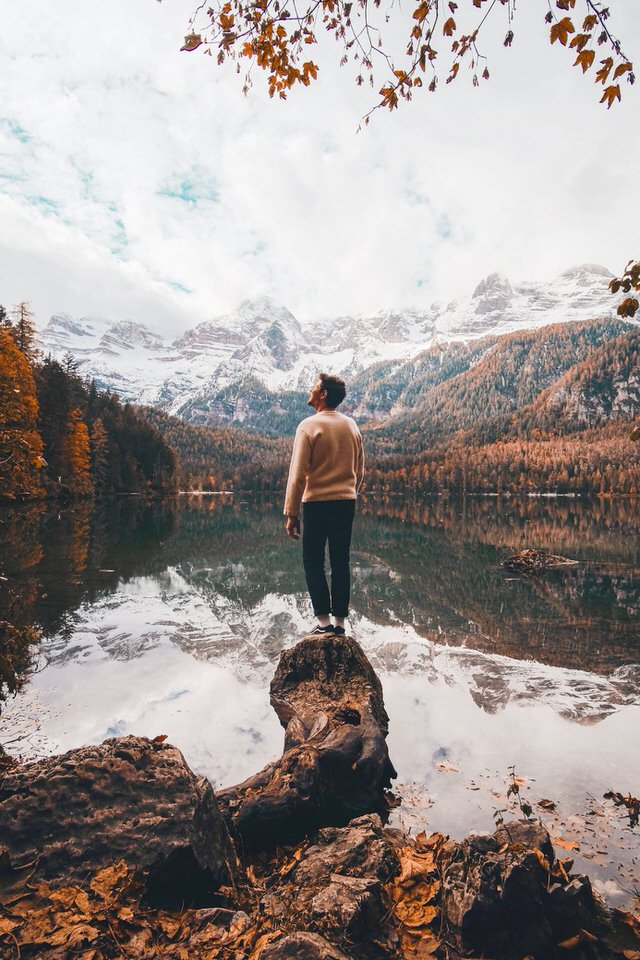 Image shows a person looking up at snow covered mountains. The lake seems perfectly still so the reflection is almost mirror like.
