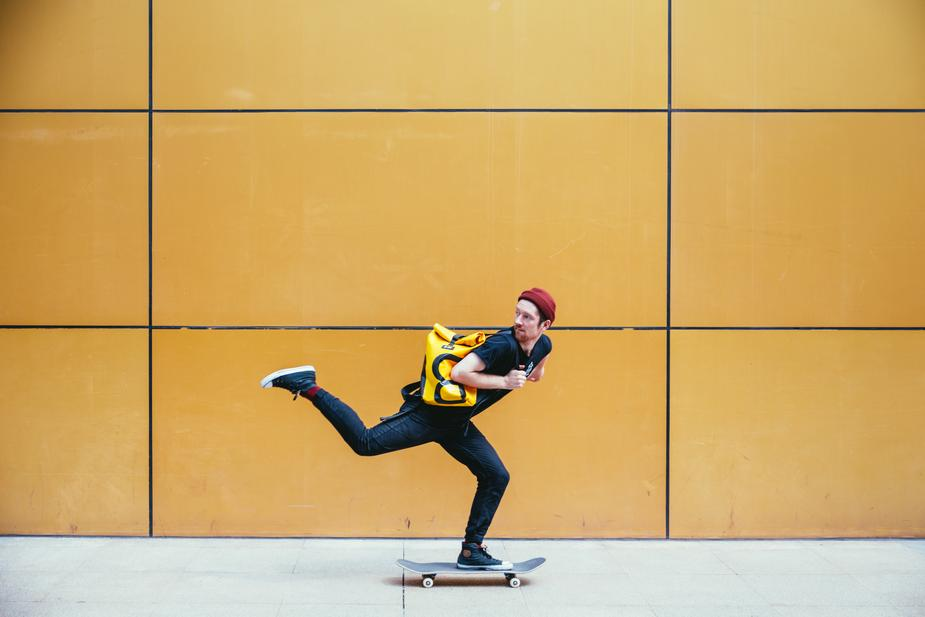 Image shows a skateboarder against a yellow wall. Your catalyst propels your story forward.
