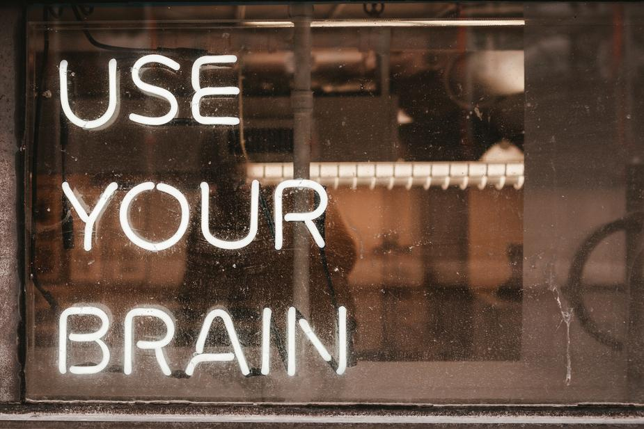 """Image shows the words """"use your brain"""" in neon lights"""