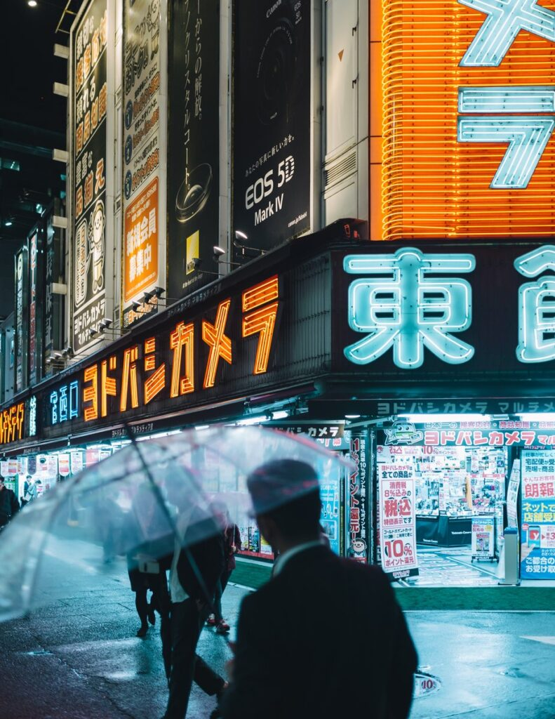 Commuters on a neon lit Tokyo street. How to go anywhere when you can't go anywhere.