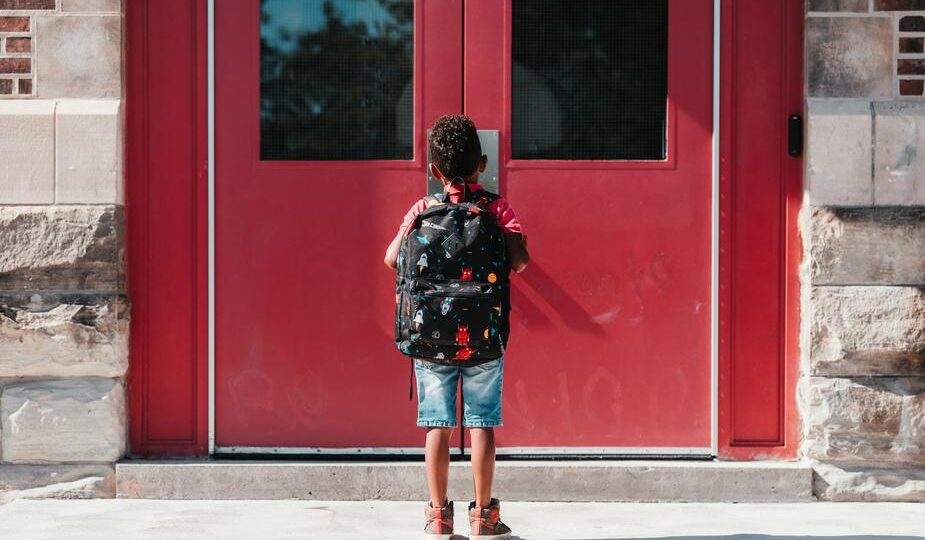 Image shows a small child in blue shorts outside a red school door. Learning is lifelong.
