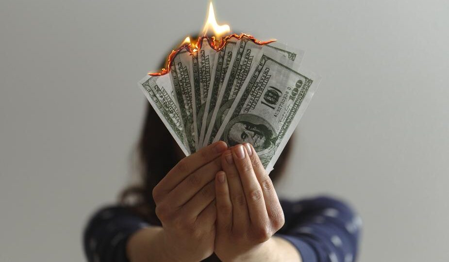 Shows a person holding burning money. Don't squander your stories or it's like burning an asset.