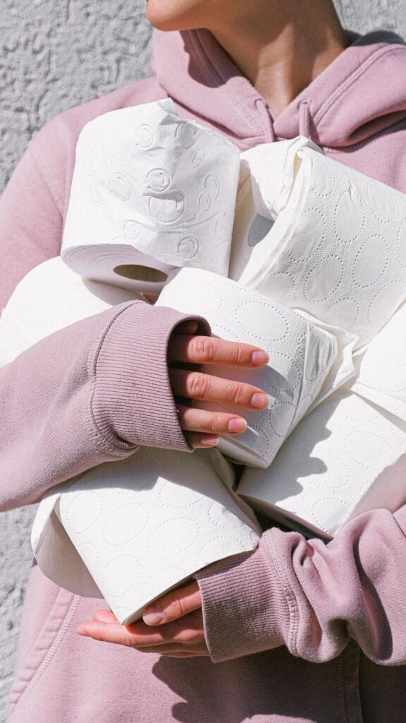 Image shows a person clutching a number of toilet rolls to their chest.